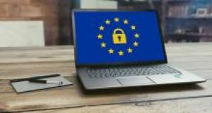 Image of computer on a desk, with an EU flag and a padlock (the GDPR logo) displayed on the computer screen
