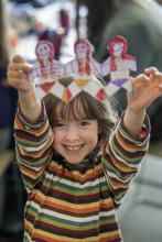 Child holds up her decorated paper chain people