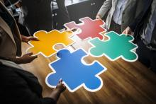 4 people holding jigsaw puzzle pieces